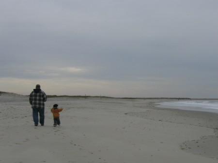 small son running to catch up with his dad on the beach