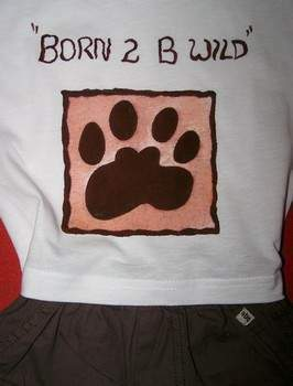"A baby's onsie with a fabric paint design of a paw and the words ""Born 2 B Wild""."