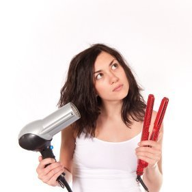 Young woman holding blowdryer and curling iron. She appears to be deciding which to use.