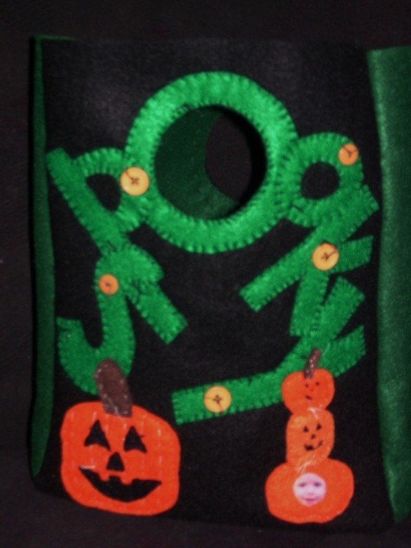 Black treat bag with green letters spelling out spooky and jack-o-lanterns.