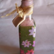 bath salt bottle wrapped in floral paper sealed with a cork top edge wrapped in tied raffia with a tag