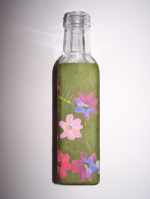 one side of bath salt bottle with flowers applied to green paper wrapped around it