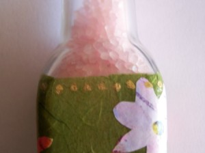 close up of bath salt bottle showing salts and oive paper wrapped around the bottle, white flower on right side gold dots along top edge of paper