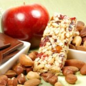An apple, granola bar, nuts and dark chocolate squares.