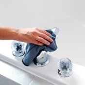 Woman's hand holding blue cloth cleaning the tub spout.