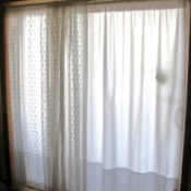 Sliding glass doors with white twin sheets as curtains behind lace curtains.
