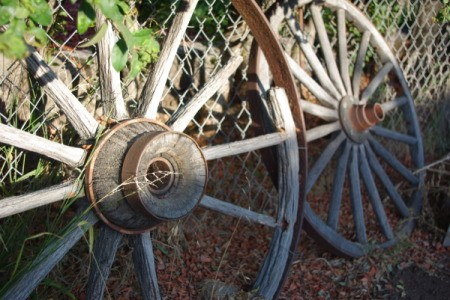 Antique Wagon Wheels Leaning Against Chain Link Fence