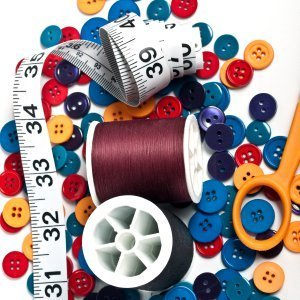Spools of thread, buttons, scissors, and a tape measure.