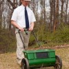 Man in tie and hard hat pushing a lawn mower