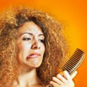 Beautiful woman with frizzy hair looking at her comb, with a pained expression