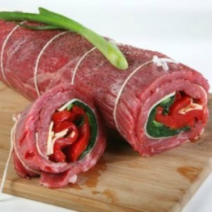 Rolled flank steak stuffed with spinach, peppers, and cheese, ready for cooking.
