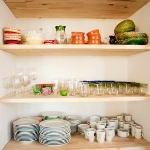 Dishes arranged inside cabinet.