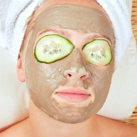 Woman with facial mask and cukes on eyes.