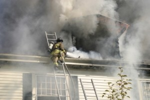 A firefighter in the smoke from a house fire.