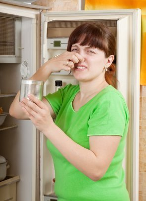 Photo of a woman holding her nose in front of her refrigerator.