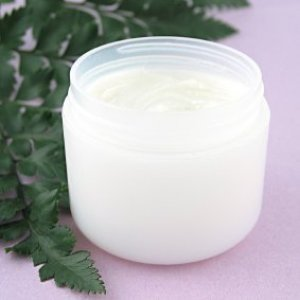 Homemade Moisturizer in a jar near a fern leaf