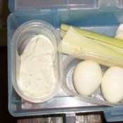 Lunch box with a Good Value container full of dip, one full of eggs, and celery and cauliflower loose in the box