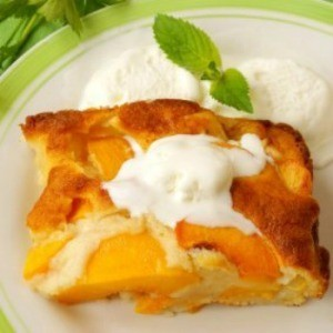 Square of peach cobbler on a plate with whipped cream on the side.