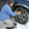 Man Putting Chains on His Car in the Snow