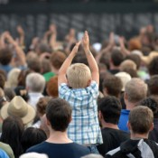 Child Clapping in Crowd at Festival