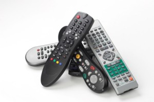 A stack of remote controls for various electronics.