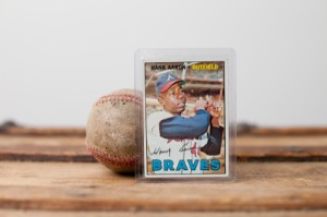 Vintage Hank Aaron Baseball Card Leaning Against Old Baseball