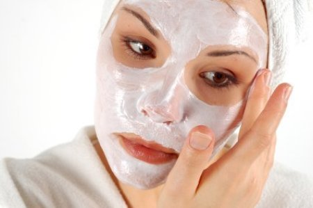 A woman applying a face mask at home.