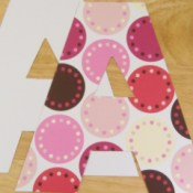 Two upper case letter A's cut out laying one on top of the other. bottom one has white side face p top on hase colorful pink and bron dots on it