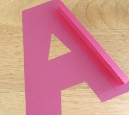 Large pink cutout of letter A with largestrip of pink cardstock glued on to form an edge