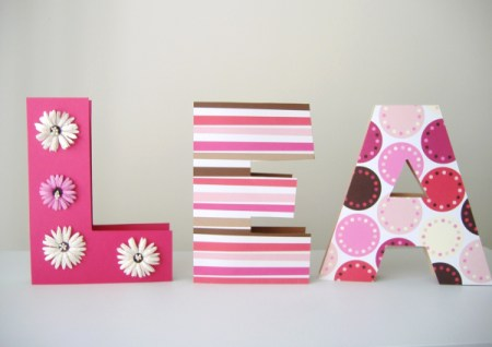 The name Lea completed as three dimensional blocks covered in patterened paper, the L has a line silk daisies going from top to bottom on th front