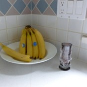 Small vase and bowl of bananas on kitchen counter