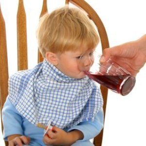 Man's hand helping a young boy drink his juice.