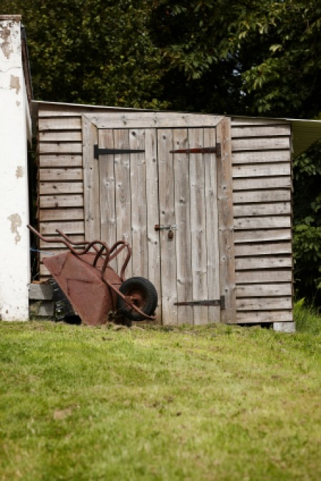 A garden shed built slightly on a hill.