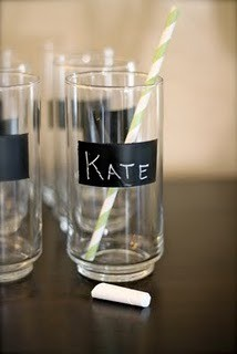 Tall Glasses with black stripe of chalkboard painted on them. The glass centered inthe image has Kate written on it, a yellow striped straw in the glass and a piece of chalk laying in front.
