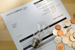 Saving Money on Your Electric Bill, Money and Light Bulb on Top of Electric Bill