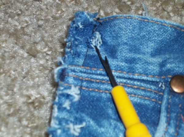 Close up of seam ripper next to jeans