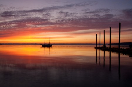 A colorful sunrise over the Puget Sound, with a boat and dock.