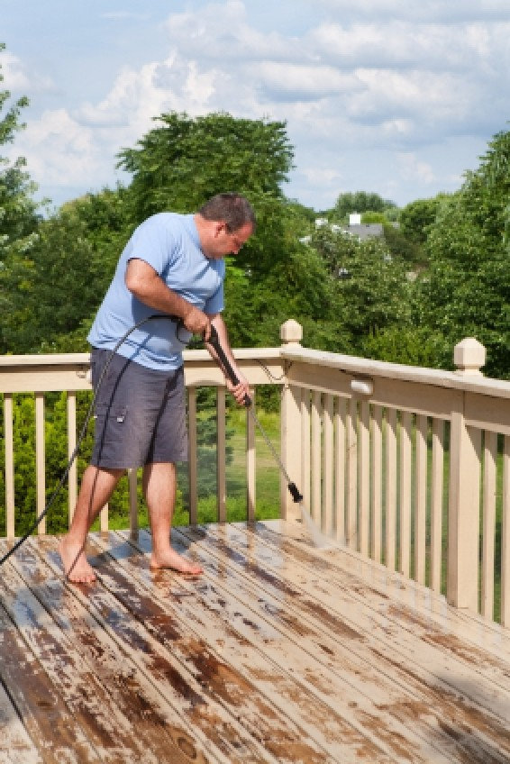 Man Pressure Washing His Wood Deck