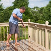 Man Pressure washing his Wood Deck