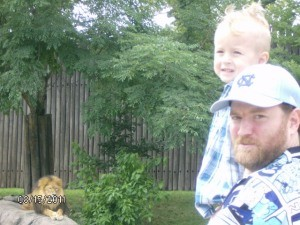 Man and Son posing in Front of Lion at Cleveland Metroparks Zoo
