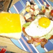 Stripped plate with two slices of bread.  Slice on the right has bacon, lettuce, tomato, and fried egg on top; slice on left has cheese.  Next to the bread is an antipasto salad.