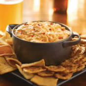 Beanpot style bowl filled with dip sitting on a tray surrounded by crackers.