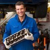 Finding an Honest Mechanic, Mechanic Holding up Car Part in Front of Car