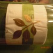 Plastic bottle toilet paper holder hung sideways with leaf design embossed on it.