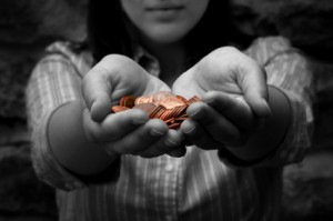 Woman Holding Out Hand Full of Pennies