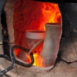 View of pottery kiln with tongs adjusting a piece.