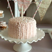 small pink cake with one candle and bunting strung across