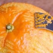 A zester being used on an orange.
