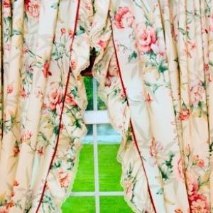 Ruffled flowery curtains on pane glass window.