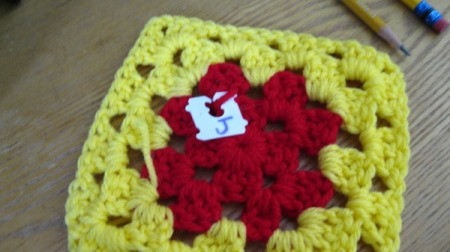 Granny square with bread closure attached, marked with a J.